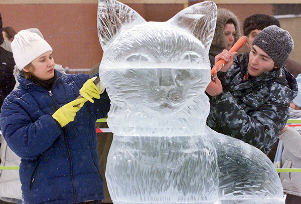 Russian students Yulia Zhdanova, left, and Anton Chebonenko, carve an ice sculpture of a cat outside the Kremlin in Moscow, Monday Dec. 30, 2002. An ice sculpture festival is being held in Moscow. (AP Photo/Mikhail Metzel)