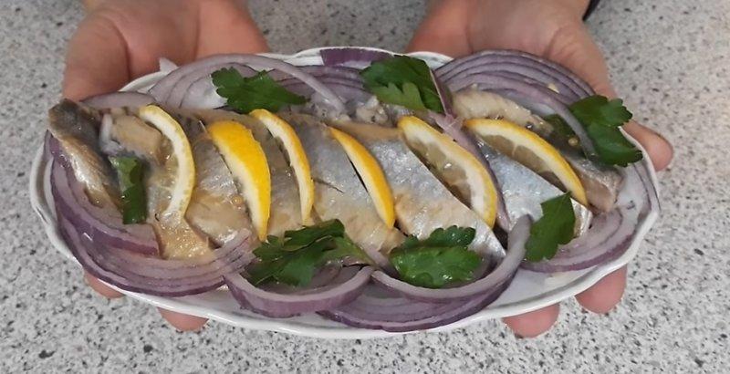 соленая селедка на тарелке